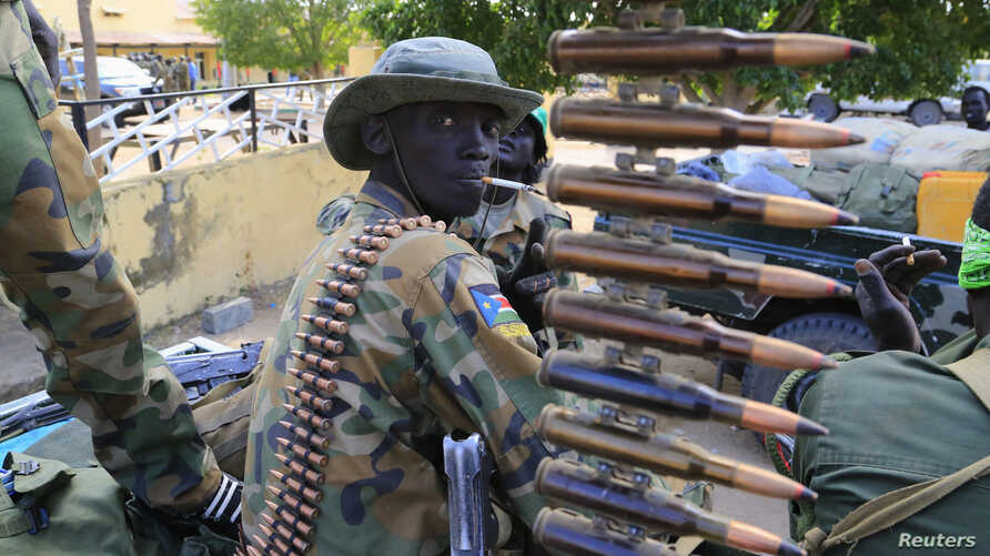 FILE - A South Sudan army soldier stands next to a machine gun mounted on a truck in Malakal town, some 500 km (312 miles) northeast of the capital, Juba.