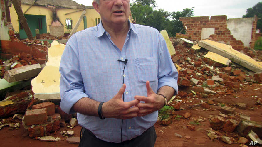 FILE - U.N. humanitarian chief Stephen O'Brien answers reporters' questions during a trip to Bangassou, Central African Republic, July 18, 2017. O'Brien warned at the time of the growing violence; more than 300 people have been killed and 150,000 dis