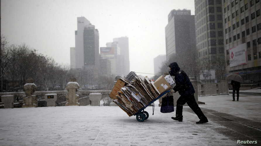 FILE - A man carries scraps in a handcart during snowfall in central Seoul, South Korea, Feb. 16, 2016. With the recycling market dimming, Seoul is turning to upcycling.