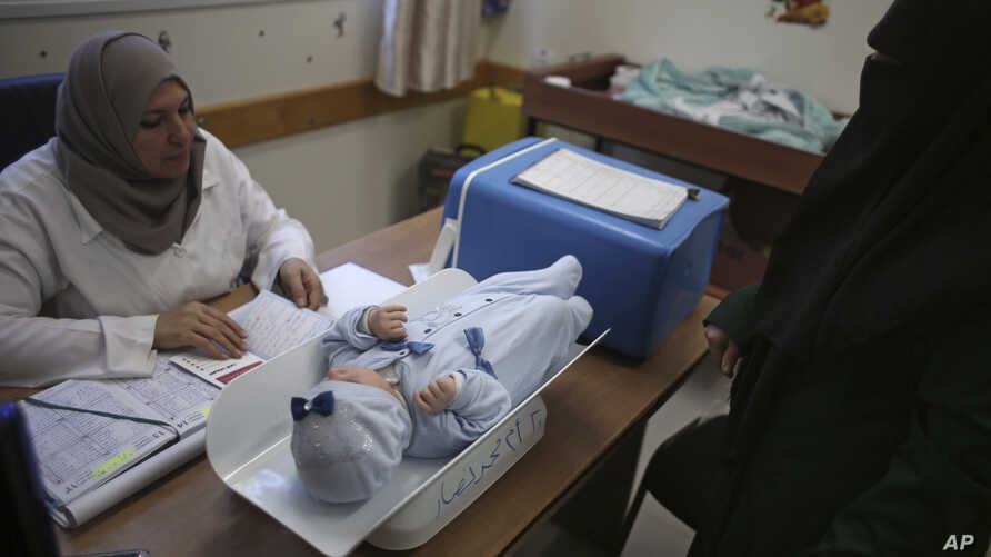A Palestinian woman has her child checked at an UNRWA-run clinic in the Shati refugee camp, Gaza City, Jan. 14, 2018.