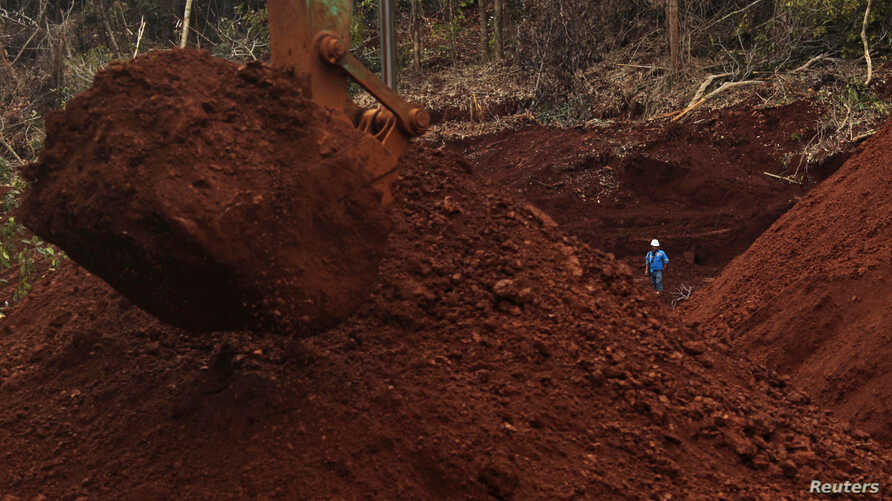 A worker stands beside an excavator digging for ore at Mobi Jaya Persada's nickel mining area at Dampala village in Marowali, central Sulawesi, Indonesia, Jan. 12, 2014.