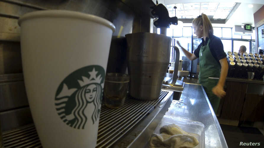 A barista makes drinks inside a newly designed Starbucks coffee shop in Fountain Valley, California August 22, 2013.  REUTERS/Mike Blake  (UNITED STATES - Tags: BUSINESS FOOD) - RTX12TYK