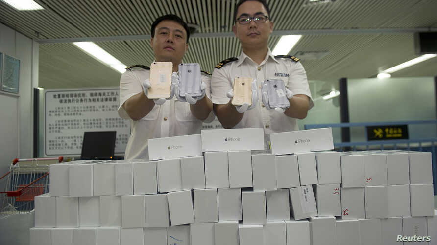 Customs officers show smuggled iPhone 6 sets, which were seized at a port in Shenzhen, China.