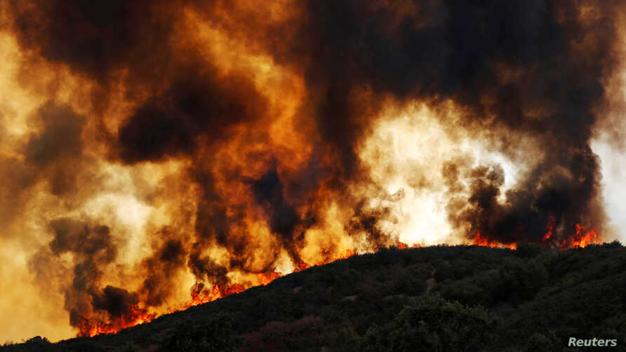 Wind-driven flames roll over a hill towards homes during the River Fire (Mendocino Complex) near Lakeport, California, U.S., Aug. 2, 2018.