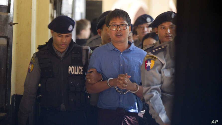 Reuters journalist Wa Lone is escorted by police as he leaves court Wednesday, Jan. 10, 2018, outside Yangon, Myanmar.
