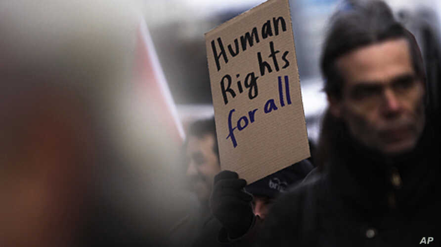 A protester holds a poster during a demonstration against racism and for human right for all people at the International Human Rights Day in Berlin,  Dec. 10, 2011.