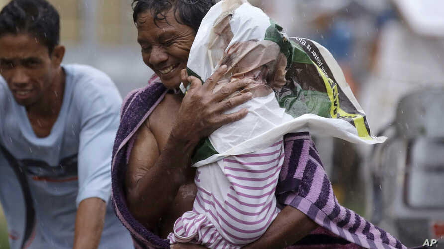 Residents of the slum community of Baseco evacuate to safer grounds at the onslaught of Typhoon Rammasun in Manila, Philippines, July 16, 2014.