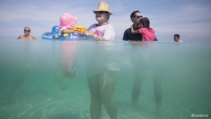Retiree Madeline Barcelo (C) holds her granddaughter surrounded by relatives at the beach in Varadero, Cuba, August 26, 2015. Cubans are flocking to the beach in record numbers before a possible end to the U.S. travel ban that would open the gates to...
