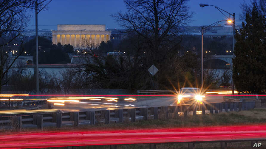 Traffic streaks along U.S. Highway 50 early in the morning, March 30, 2018 across the Potomac River from Washington in Arlingotn, Va. The Trump administration is expected to announce that it will roll back automobile gas mileage and pollution standar