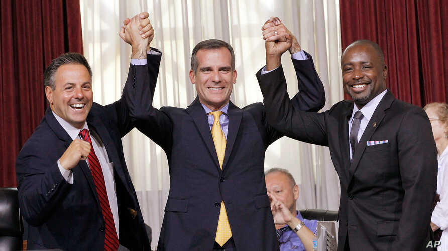 Los Angeles Councilman Joe Buscaino, left, Mayor Eric Garcetti, center, and Councilman Marqueece Harris-Dawson celebrate after a council vote that cleared the way for Garcetti to strike agreements for a 2024 Olympics bid, Sept. 1, 2015.