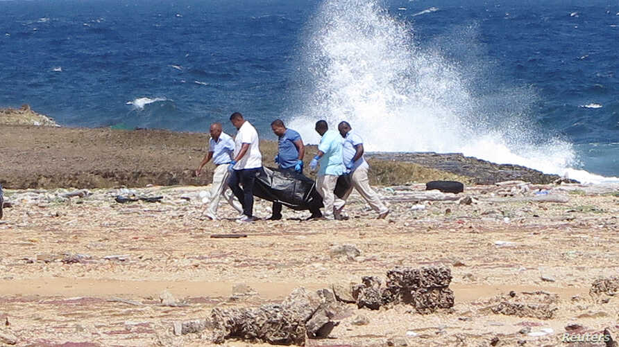 Forensic workers carry a bag containing the body of a person who was found at the shore, near Willemstad, Curacao, Jan. 10, 2018.