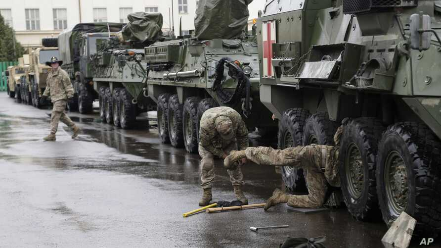 FILE - U.S. Army soldiers perform maintenance on an armored vehicle during a stop of their convoy in Prague, Czech Republic, March 31, 2015. The convoy started from Estonia and also passed through Latvia, Lithuania and Poland before returning to a Ge
