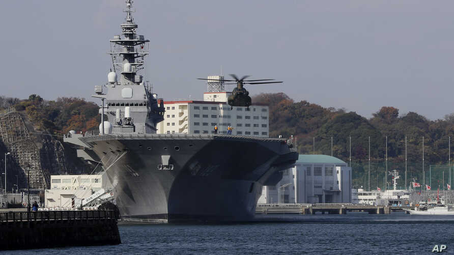 FILE - A helicopter of Japan Self-Defense Forces prepares to land on the flight deck of the helicopter destroyer Izumo of Japan's Maritime Self-Defense Force (JMSDF) following the visit by United States Secretary of Defense Ash Carter in Yokosuka, so