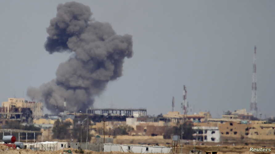 FILE - A plume of smoke rises above a building after an airstrike by the U.S.-led coalition battling the Islamic State group, in Tikrit, Iraq, March 27, 2015.