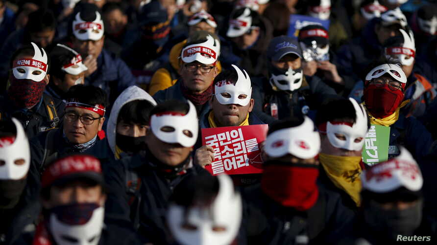 "Masked protesters participate in an anti-government rally in central Seoul, South Korea, Dec. 5, 2015. The sign in center reads: ""Listen to people's voice."""