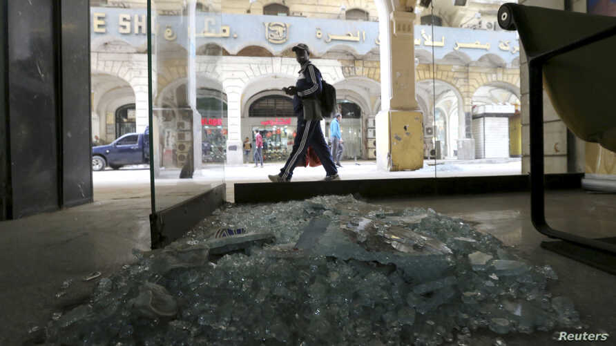 A passerby inspects the site of a blast that hit central Cairo Tuesday. A man was killed in a bomb blast in Alexandria, Egypt, hours after two devices were discovered at Cairo airport, Feb. 3, 2015.