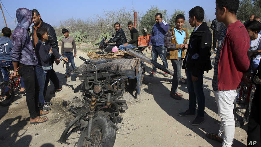 FILE - In this Monday, Nov. 12, 2018 file photo, Palestinians inspect a vehicle that was destroyed in an Israeli raid that killed seven Hamas Palestinian militants, including a local Hamas commander, late Sunday, east of Khan Younis, southern Gaza St