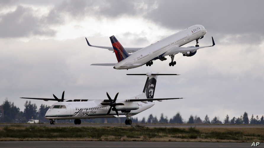 A Delta jet takes off in view of an Alaska Airlines plane that just landed Dec. 16, 2015, at Seattle-Tacoma International Airport, in  Washington. A process developed by the U.S. Department of Energy's Pacific Northwest National Laboratory could turn