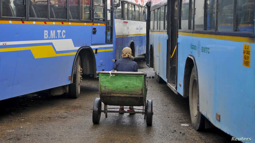 FILE - A porter sits in his pushcart as he waits for customers in between passenger buses at a municipal bus terminal in Bengaluru, India, September 8, 2015.
