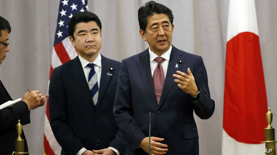 Japanese Prime Minister Shinzo Abe, right, answers questions from the media after meeting with then U.S. President-elect Donald Trump during his stopover in New York, Nov. 17, 2016. Abe was en route to an APEC meeting in Lima, Peru.