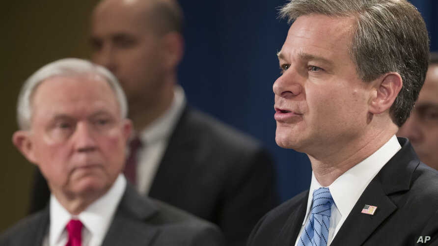Attorney General Jeff Sessions listens as FBI Director Christopher Wray speaks during a news conference about the arrest of Cesar Sayoc, 56, of Aventura, Fla., in the package bomb case, at the Department of Justice, Oct. 26, 2018, in Washington.