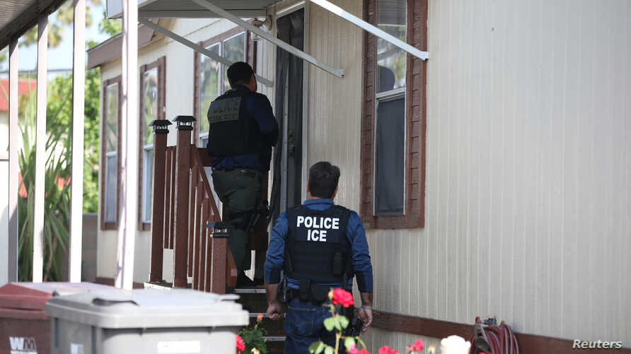 FILE - A U.S. Immigration and Customs Enforcement Fugitive Operations team searches for an immigration fugitive in Santa Ana, Calif., May 11, 2017.