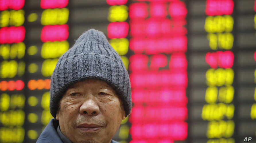 An investor sits in front of the stock price monitor at a private securities company in Shanghai, China, November 22, 2012.
