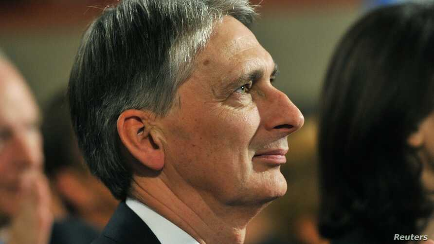 Britain's Defence Secretary Philip Hammond listens as Prime Minister David Cameron delivers his keynote speech at the Conservative Party conference in Birmingham, central England, October 10, 2012.