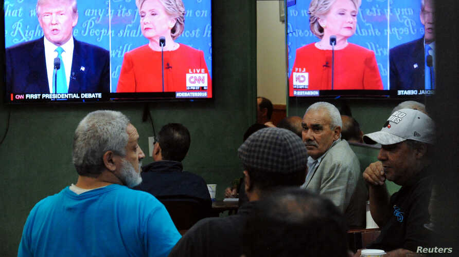 People watch the U.S. presidential debate in a restaurant in the Queens borough of New York City, Sept. 26, 2016.