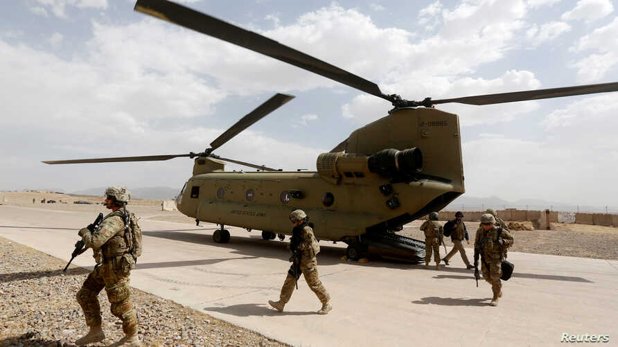 U.S. troops walk from a Chinook helicopter in Uruzgan province
