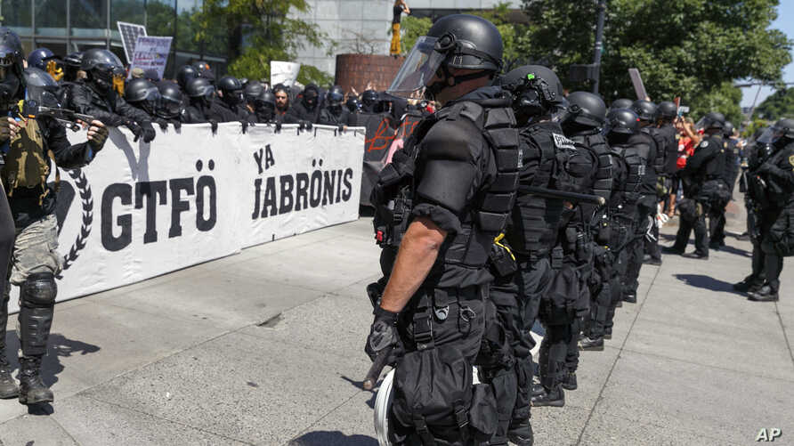 """Portland police keep Patriot Prayer affiliates separate from antifa protesters during a rally in Portland, Ore., Saturday, Aug. 4, 2018.Small scuffles broke out Saturday as police in Portland, Oregon, deployed """"flash bang"""" devices and other means to"""