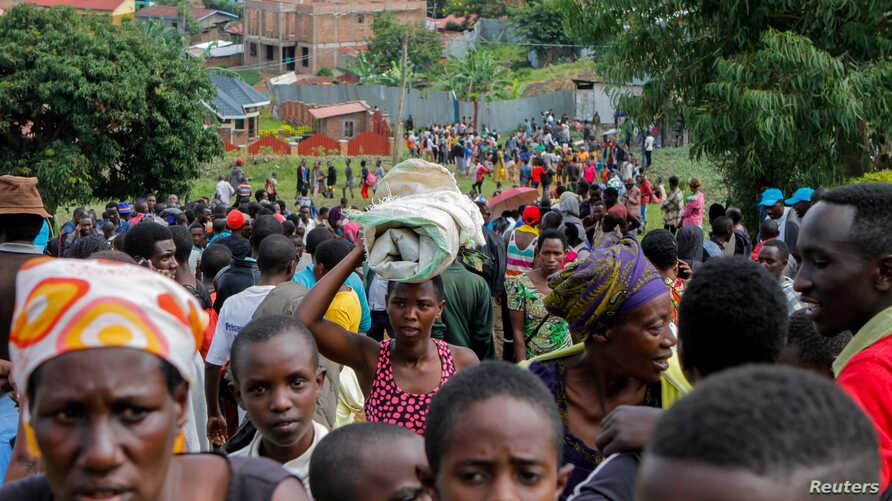 Refugees from the Democratic Republic of the Congo carry their belongings as they walk near the U.N. High Commissioner for Refugees offices in Karongi district, Rwanda, Feb. 21, 2018.