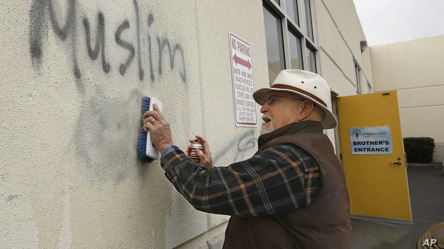 Tom Garing cleans up racist graffiti painted on the side of a mosque in what officials are calling an apparent hate crime, Feb. 1, 2017, in Roseville, Calif. The Tarbiya Institute was spray-painted with a dozen obscene and racist slurs. Garing, a ret