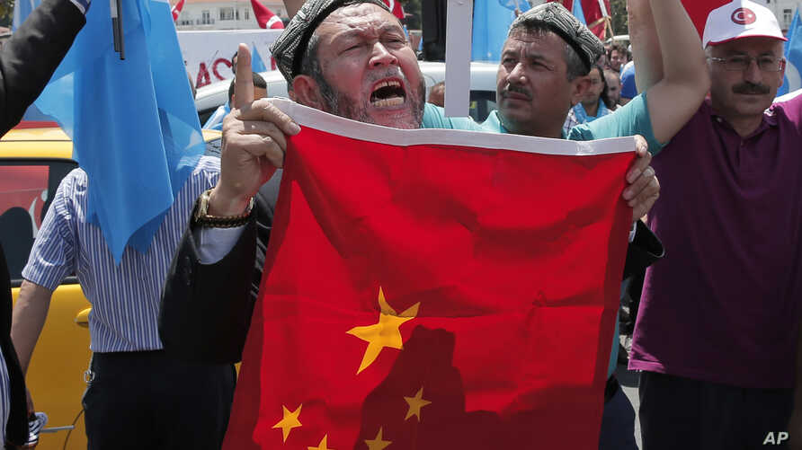 FILE - Uighurs living in Turkey and Turkish supporters, chant slogans as they hold a Chinese flag before burning it during a protest near China's consulate in Istanbul, against what they call oppression by Chinese government to Muslim Uighurs in far-