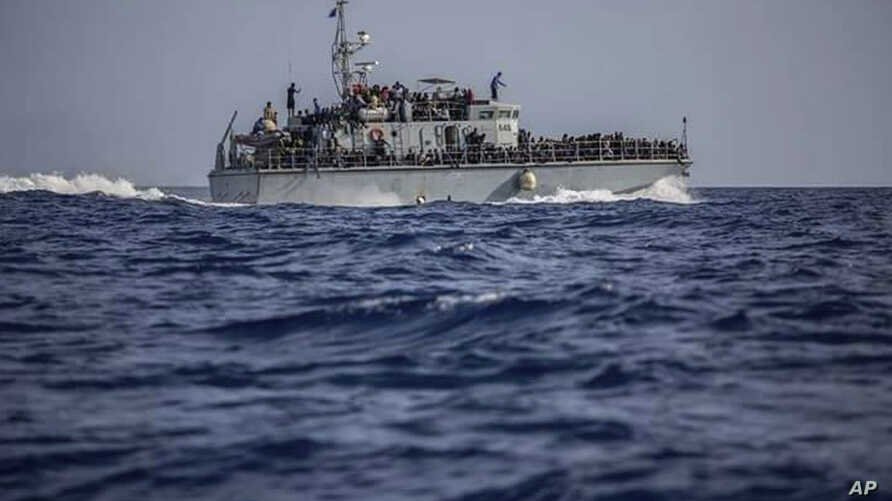 FILE - A photo released by the Libyan Coast Guard shows a ship with migrants off the coast of Libya, June 24, 2018.