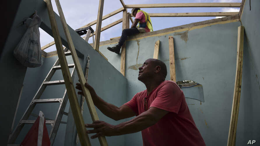 Pedro Deschamps helps workers hired by FEMA to carry out the installation of a temporary awning roof at his house, which suffered damage during Hurricane Maria, in San Juan, Puerto Rico, Nov. 15, 2017.