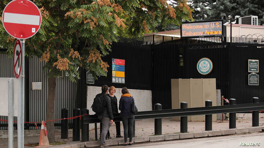 People wait in front of the visa application office entrance of the U.S. Embassy in Ankara, Turkey, Oct. 9, 2017.