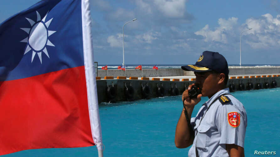 FILE - A member of the Taiwanese Coast Guard stands next to a Taiwanese flag on Itu Aba, which the Taiwanese call Taiping, at the South China Sea, Nov. 29, 2016.