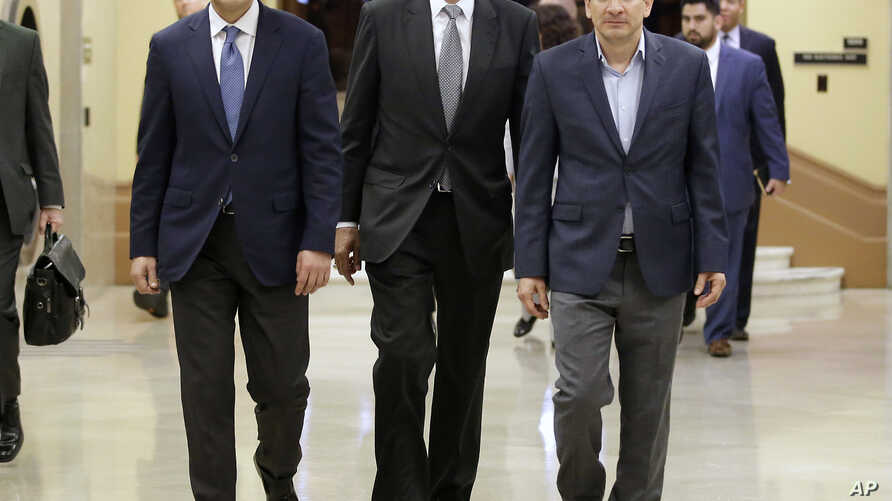 FILE - Former U.S. Attorney General Eric Holder, center, flanked by California Senate President Pro Tem Kevin de Leon, D-Los Angeles, left, and Assembly Speaker Anthony Rendon, D-Paramount, walks to a meeting with California Gov. Jerry Brown in Sacra