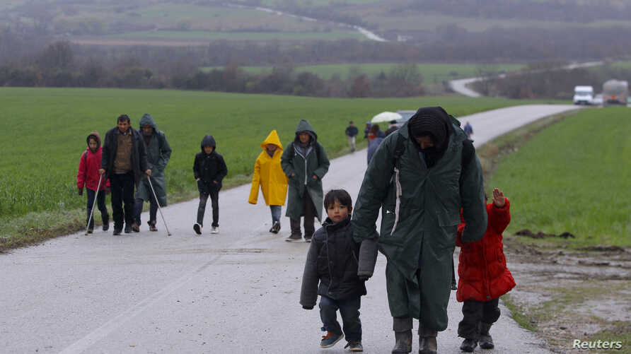 Migrants walk along a road from the village of Chamilo to the migrant camp at the village of Idomeni, near the Greek-Macedonian border, Greece, March 15, 2016.