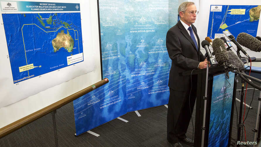 John Young, general manager of the emergency response division of the Australian Maritime Safety Authority, answers a question as he stands in front of a diagram showing the search area for flight MH370 during a briefing in Canberra March 20, 2014.