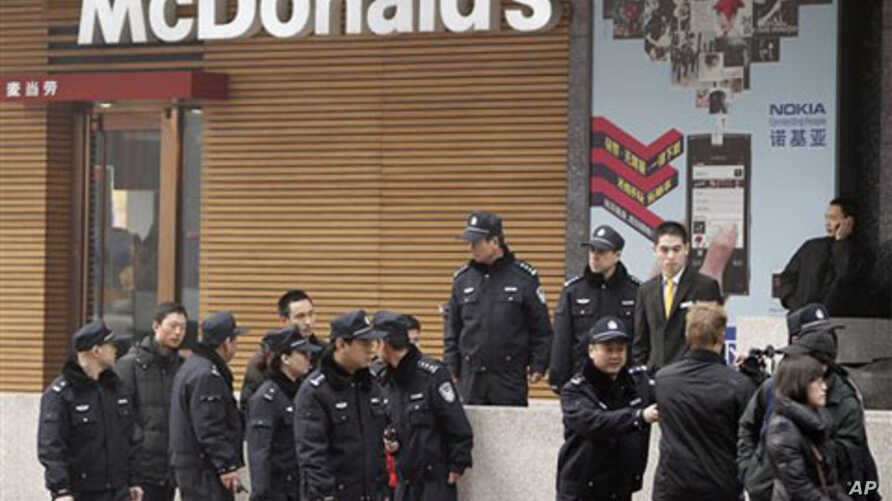 Police officers ask a journalist, lower right, to leave as he covers people gathering in front of a McDonald's restaurant which was a planned protest site in Beijing, February 20, 2011.