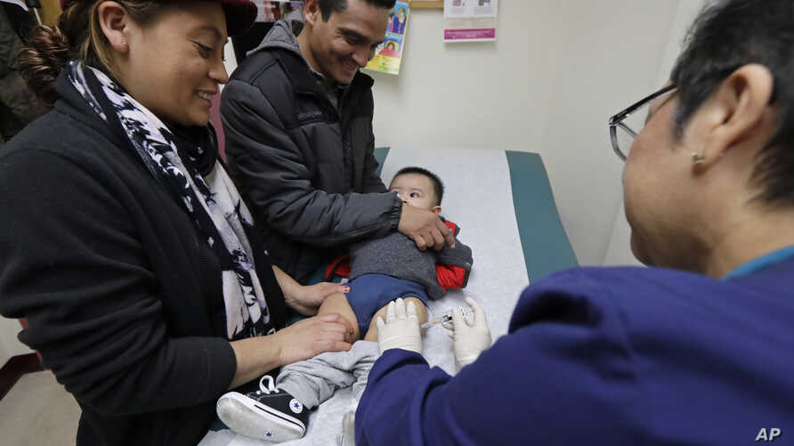 FILE - Matilde Gonzalez, left, and Cesar Calles, hold their son, Cesar Julian Calles, 10 months old, as Ana Martinez, a medical assistant at the Sea Mar Community Health Center, gives him a flu shot in Seattle, Jan. 11, 2018.
