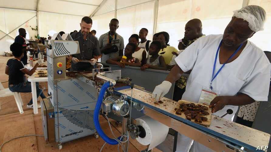 FILE - Visitors watch as employees of a Chocolatier in the Ivory Coast explain and show the different stages of processing cocoa into chocolate during the 5th edition of the ice cream and chocolate festival in Abidjan on May 19, 2018.