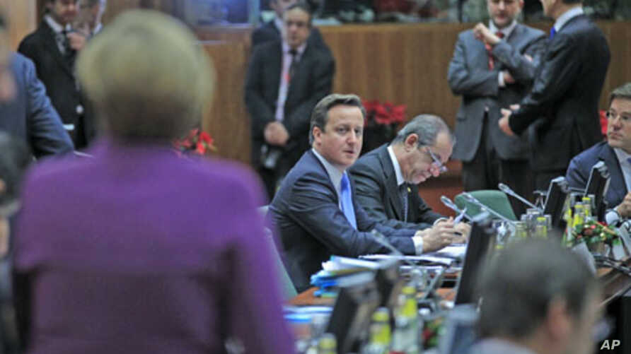 Britain's Prime Minister David Cameron (C) looks at Germany's Chancellor Angela Merkel (L) at a European Union summit in Brussels, December 9, 2011.