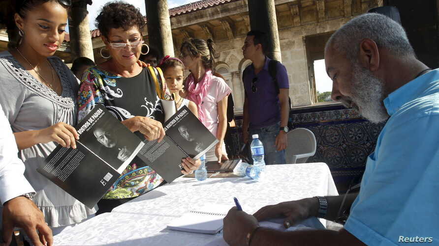 "FILE - Cuban author Leonardo Padura autographs his book ""The Faces of Padura"" in Havana, October 31, 2015. Previously, Padura was awared the 2015 Princess of Asturias award for literature."