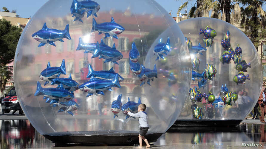 """A boy looks at fish-shaped balloons installed in a water fountain to mark April Fools' Day, called """"Poisson d'Avril"""" in France, in the centre of Nice, April 1, 2015."""