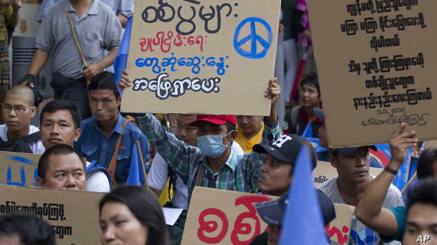 FILE - Activists shout slogans and brandish placards demanding a stop to the war, as they take part in a rally for peace, May 12, 2018, Yangon, Myanmar.