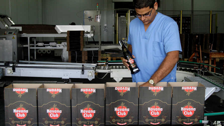 FILE - a worker checks the production of Havana Club rum at the company's factory in Havana, Cuba.