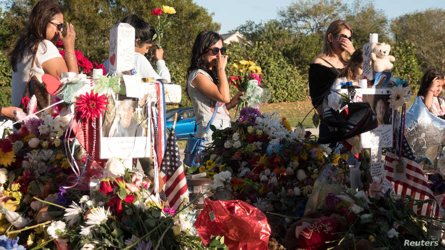 Well-wishers place mementos the day students and parents arrive for voluntary campus orientation at the Marjory Stoneman Douglas High School, for the coming Wednesday's reopening, following last week's mass shooting in Parkland, Florida, Feb. 25, 201...